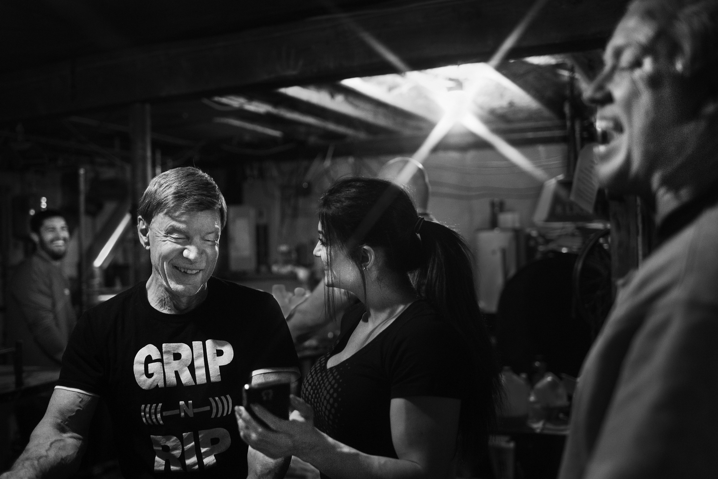 Devio and other arm wrestlers laugh at videos on fellow arm wrestler Valerie Beach's phone on March 3, 2016, in Fitzsimmons' basement in West Bridgewater, Massachusetts. (Photo by Adam Glanzman/GroundTruth)