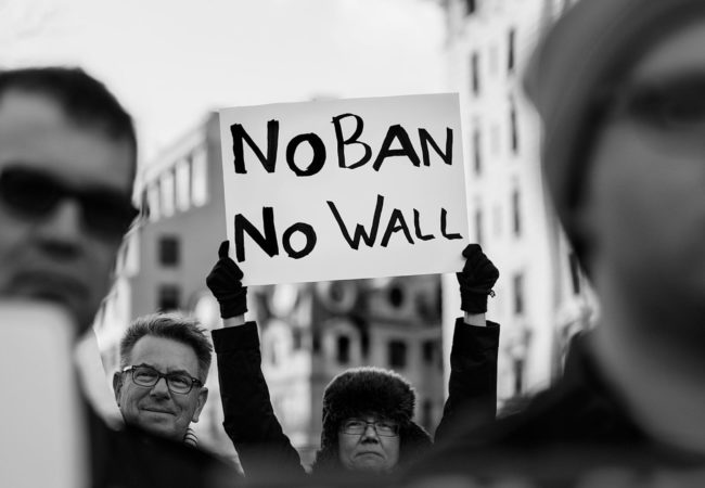 "A protester holds up a sign that reads, ""No ban, no wall"" at a rally against President Trump's ""Muslim Ban"" on Jan. 26, 2017. (Photo by Lorie Shaull/Wikimedia Commons)"