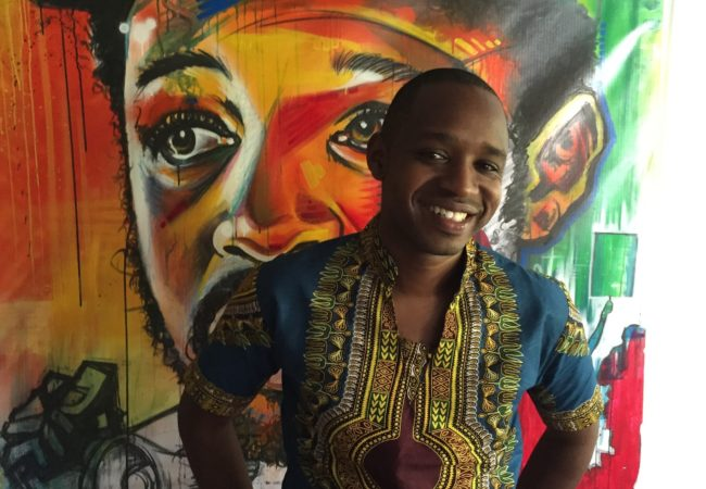 Boniface Mwangi stands in front of a painting in PAWA254, an artspace and office.
