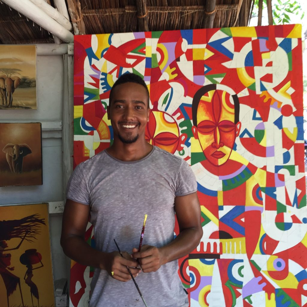 Artist Kevin Peters poses with a cubist painting he created in Diana Beach, Kenya. (Photo by Kevin Grant/GroundTruth)