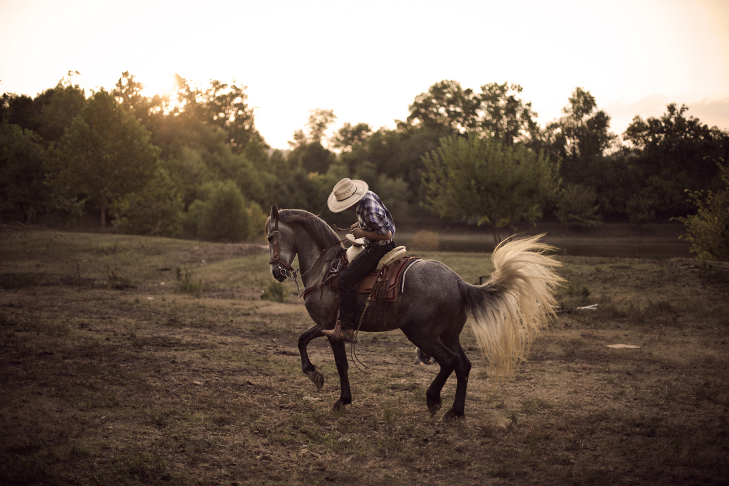 Marcos Espinoza, 17, goes for his daily ride on his favorite horse, Maximo, at the family ranch in Bowling Green, Kentucky. Marcos is the son of immigrant parents from Guatemala and Mexico, and he wants to carry on the legacy of his culture in the United States. (Photo by Betina Garcia/GroundTruth)