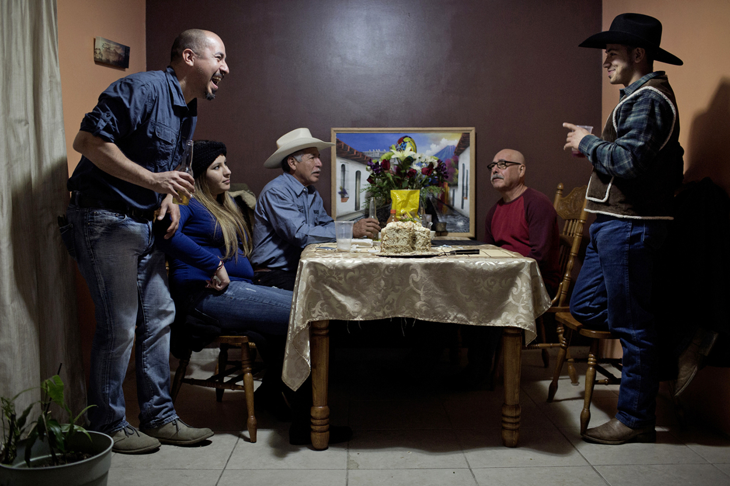 Juan Barillas (left) laughs at a joke with his nephew, Marcos Espinoza, 17 (right), at a family surprise party in Bowling Green, Kentucky. Juan's girlfriend, Blanca Lopez, a 23-year-old Mexican girl, is next to him – she's carrying the couple's first child. In the back, Manuel Barillas enjoys conversation with his brother, Edwin Barillas. (Photo by Betina Garcia/GroundTruth)
