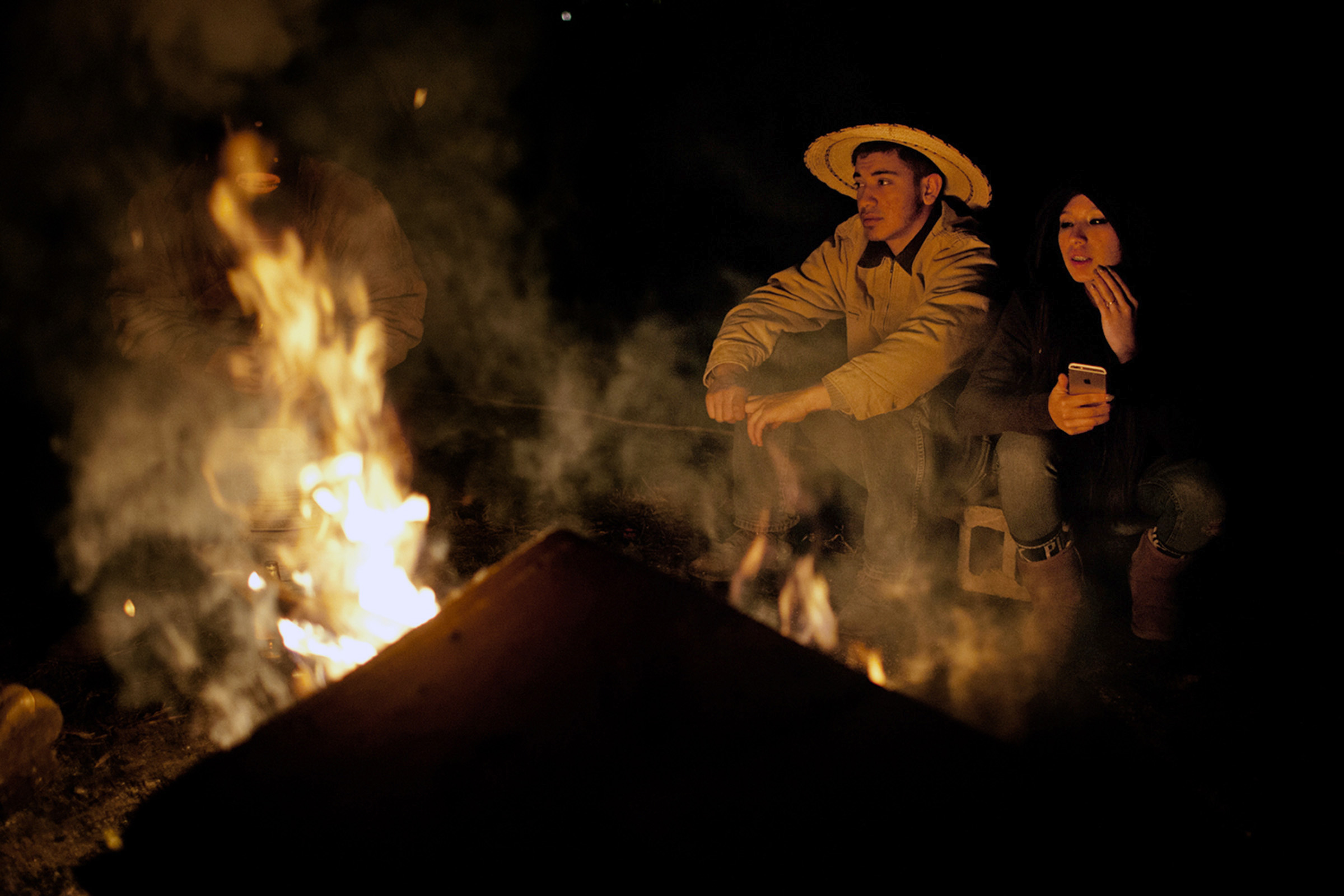 Marcos Espinoza, 17, enjoys a quiet Saturday night in front of the bonfire with his friend, Hector Garduno (left) and his cousin, Elisa Yamileth, 15, on the family ranch in Bowling Green, Kentucky. Espinoza wanted to live on the ranch so that he could be closer to the family. (Photo by Betina Garcia/GroundTruth)