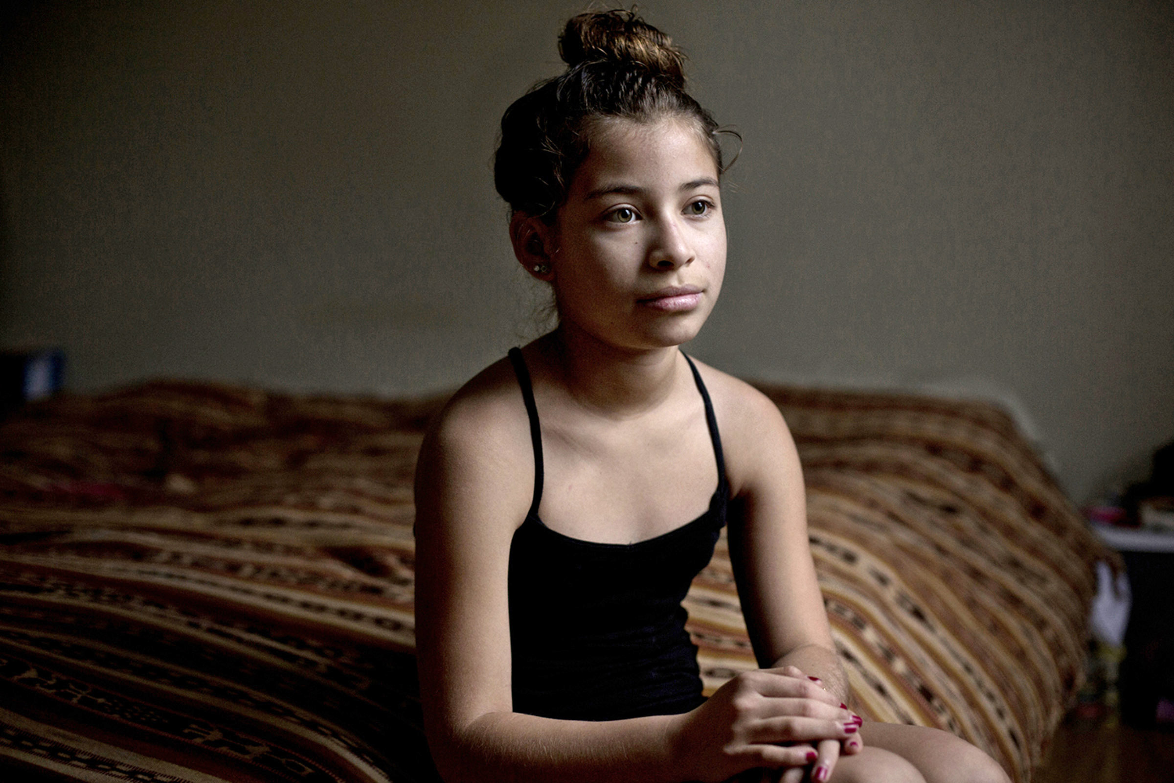 Nayda Espinoza, 12, poses for a portrait in her bedroom on the family ranch in Bowling Green, Kentucky. Nayda is sharing her bedroom with her parents until the family is done expanding the house. (Photo by Betina Garcia/GroundTruth)