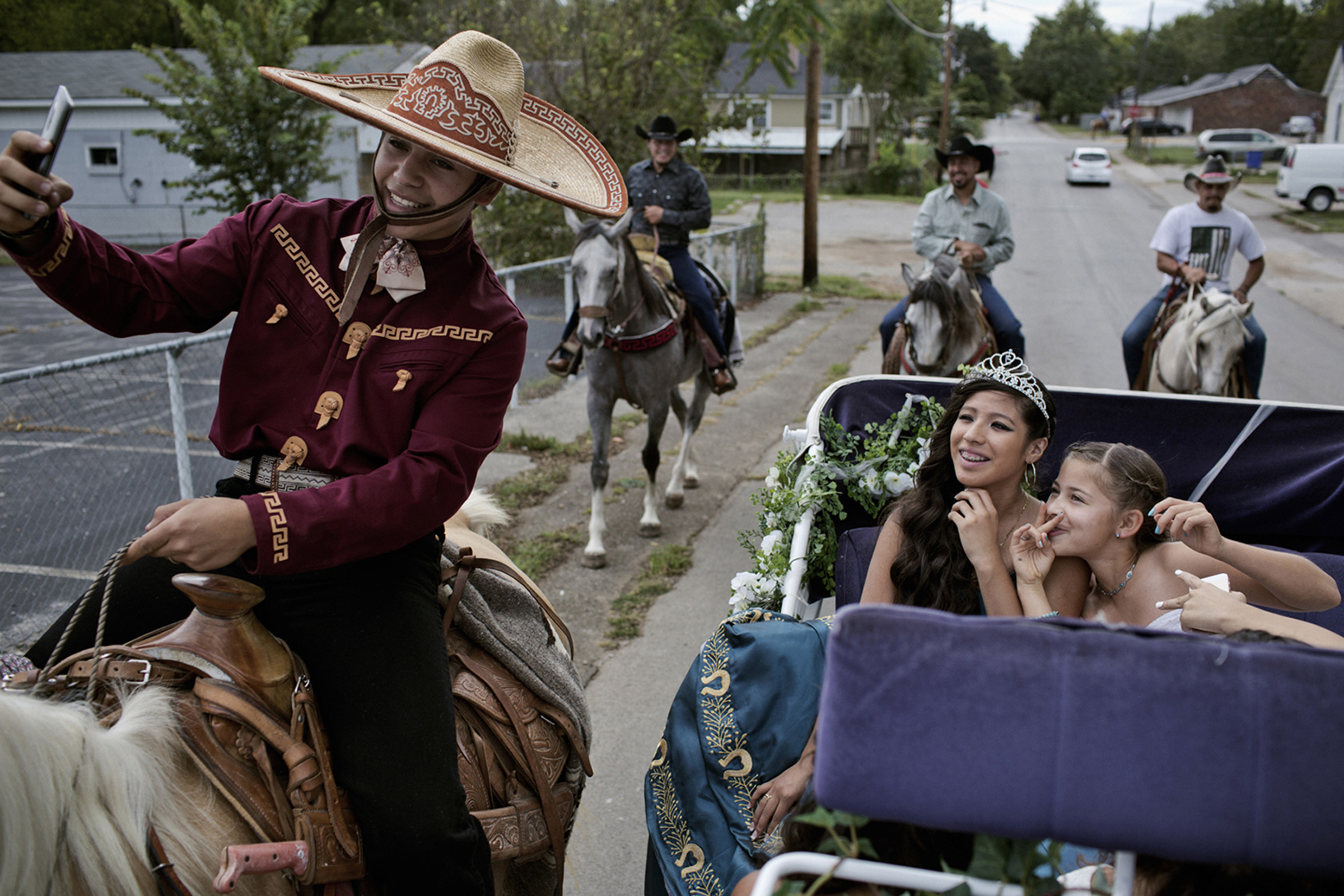 Elisa Yamileth poses for a selfie on her 15th birthday, riding in a horse-drawn carriage along with her 12-year-old cousin, Nadya Espinoza. Her other cousin, Francisco Espinoza, gets in the shot, too. (Photo by Betina Garcia/GroundTruth)