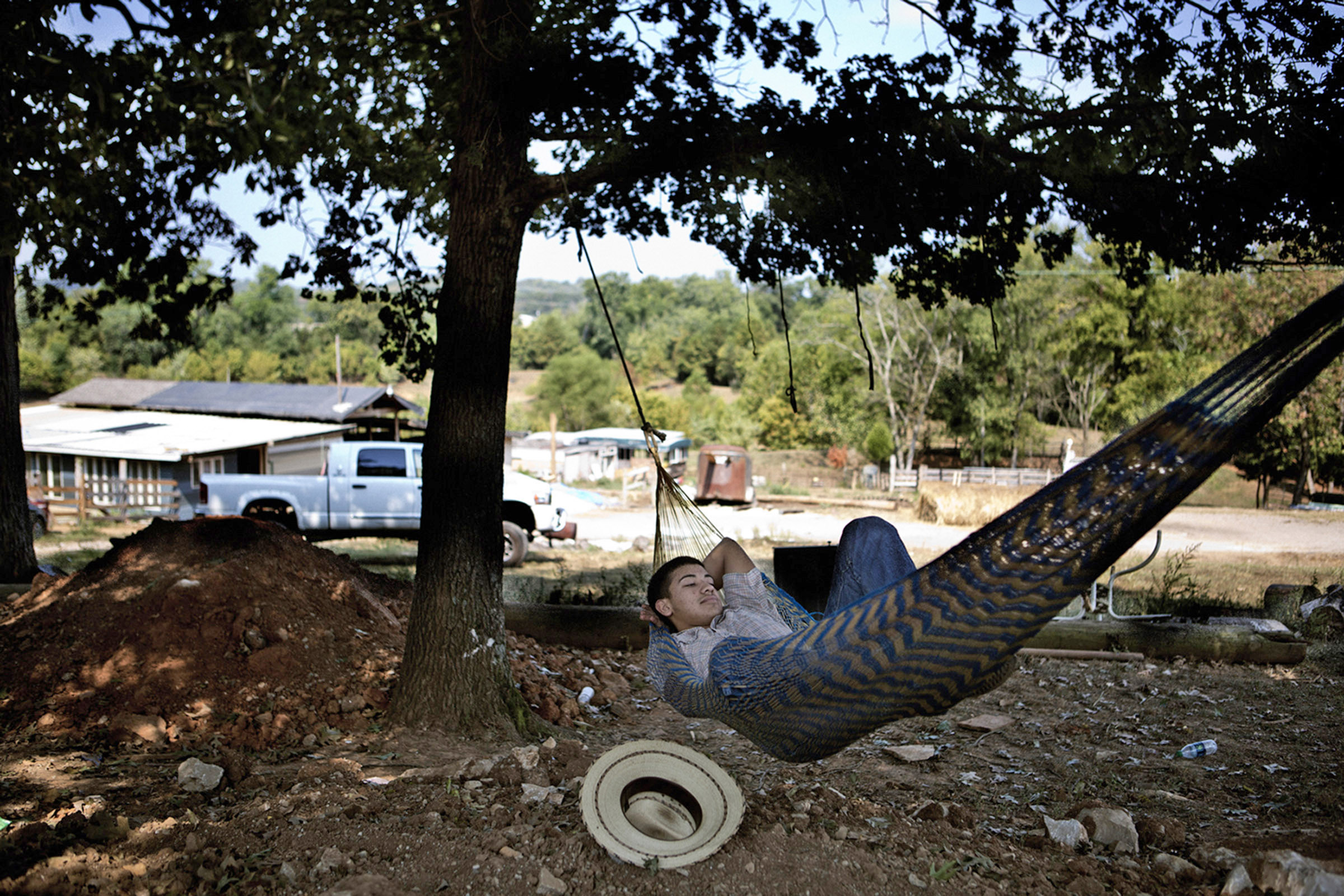 Marcos Espinoza, 17, rests in a hammock on a Sunday morning at the family ranch in Bowling Green, KY . His parents go to Iglesia La Hermosa, a Hispanic church every Sunday. They try to make him and his siblings go too, but they wonÕt force them. (Photo By Betina Garcia/Groundtruth).