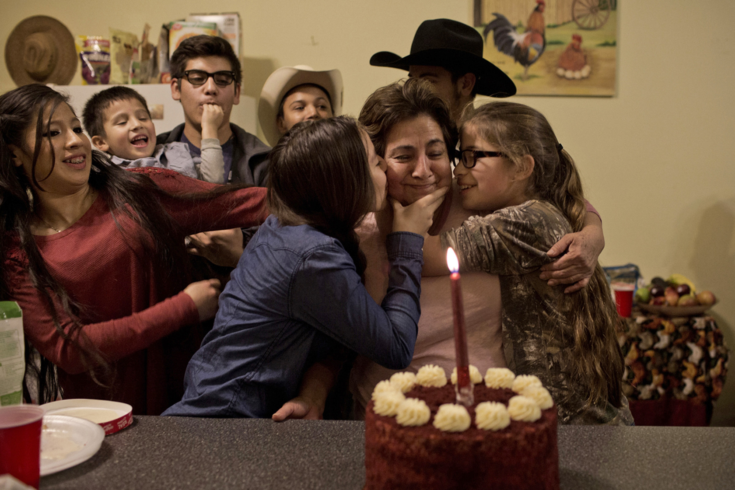 "The family celebrates at a surprise party for their grandmother, Elisa Barillas, at the family ranch in Bowling Green, Kentucky in January 2016. Barillas' grandchildren, Samantha Yamileth, 13, and Nayda Espinoza, 12, kiss her before she blows out the candle while the rest of the grandchildren sing ""Happy Birthday"" in Spanish. (Photo by Betina Garcia/GroundTruth)"
