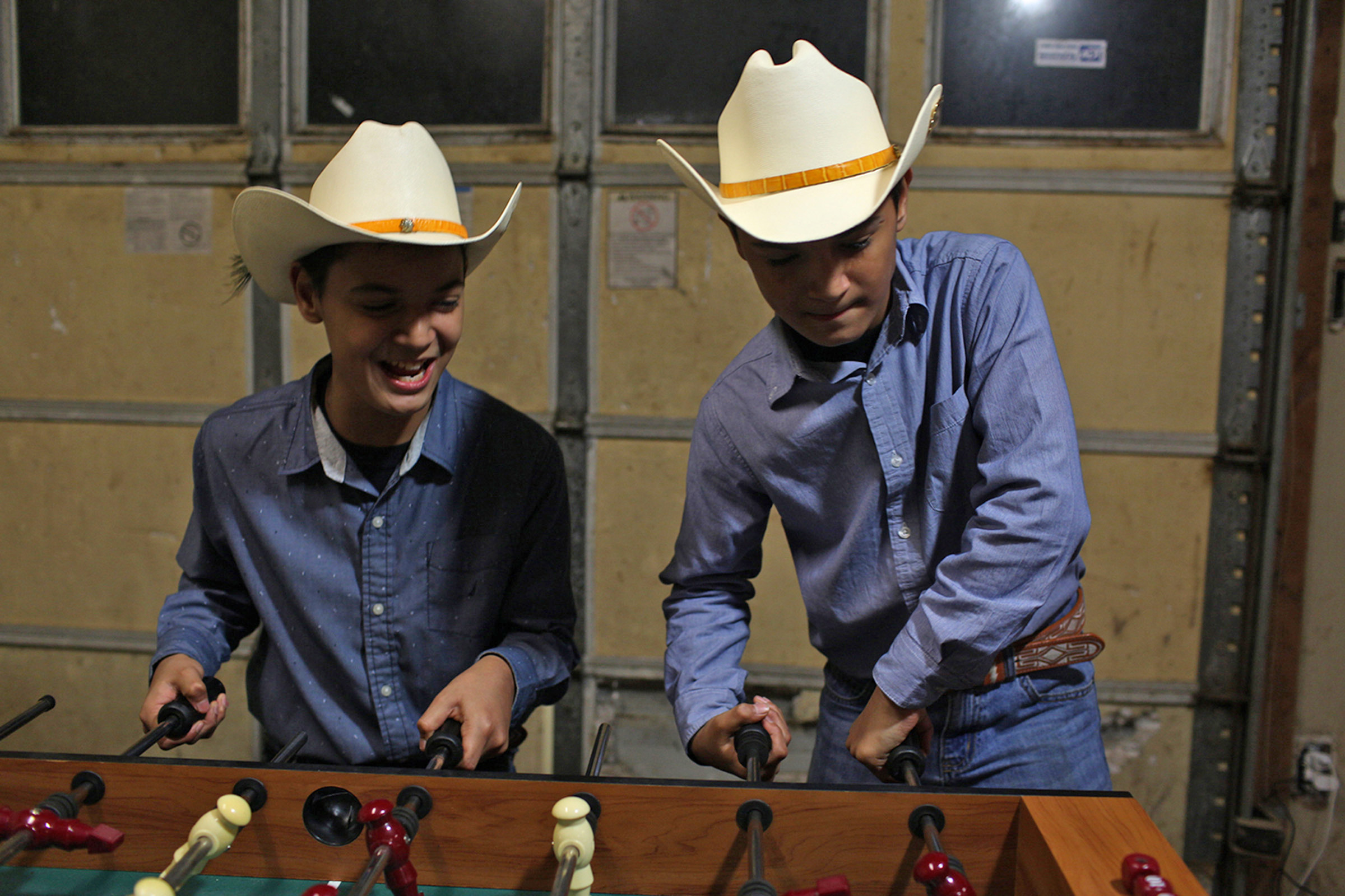 At a party the 12-years old twins Jared Valuenza, left, and Fabian Valuenza, right, played foosball on the family ranch in Bowling Green, KY in January, 2016. (Photo By Betina Garcia/Groundtruth).