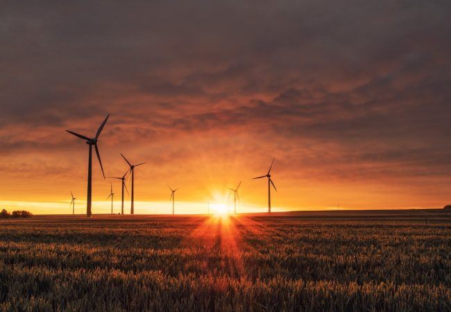 Wind turbines spin through sunset hours (Photo via Creative Commons).