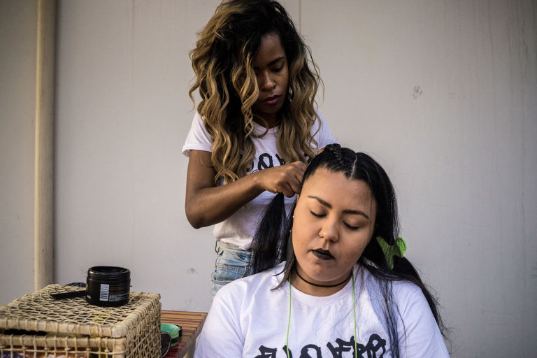 Hairstylist Alessandra Rodrigues, who works at a salon in Rio's north side, creates a boxer braid backstage at Yas Werneck's show. (Photo by Leonardo Coelho/GroundTruth)