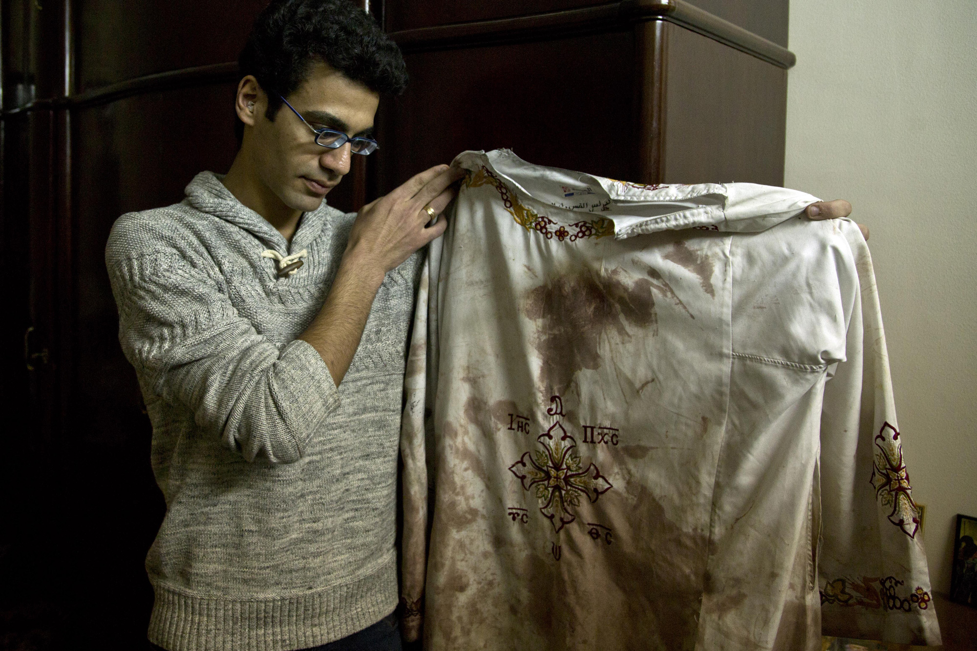 Kirollos is the brother of Bishoy Danial who died in the Palm Sunday suicide bombing in Tanta. He is holding the vestment that his father, Priest Daniel, wore during the attack. Tanta, Egypt, April 12, 2017 (Photo by Roger Anis/GroundTruth)
