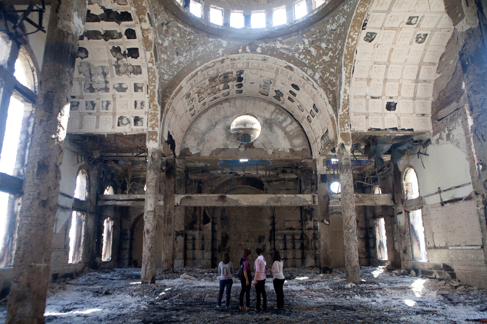Four women stand in the heavily damaged St. Mousa church in Minya, Egypt, on August 22, 2013. That year, the temple was one of the dozens of churches, businesses and homes that were burned during a surge of violence against Egypt's Christian minority.(Photo by Heidi Levine/Sipa Press).