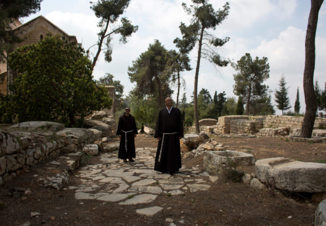 Father Salem Yunis, from Aleppo, Syria, and Father Oscar Rodriguez, from El Salvador, stand on the remnants of an ancient Roman road in Emmaus, which today lies in West Bank territory. (Photo by Heidi Levine/GroundTruth)