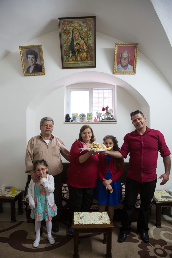 Anton Qulibyoba Yoakim (left) with his wife, son and granddaughters, as they hold a platter of Maamoul cookies, traditionally served in the Easter holiday. Their family was among the last remaining Christians in the biblical village of Emmaus, where Anton grew up. He now lives with his family in the old City of Jerusalem. (Photo by Heidi Levine/ GroundTruth)