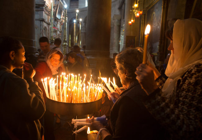 Christian pilgrims light candles during Easter Sunday at the Church of the Holy Sepulchre, traditionally believed by Christians to be the site of the crucifixion and burial of Jesus Christ. Thousands of Christians from across the world flocked to Jerusalem to commemorate Easter. Jerusalem, April 16, 2017 (Photo by Heidi Levine/GroundTruth).