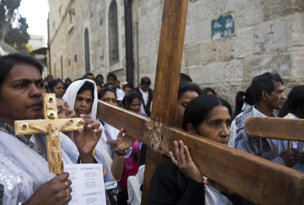"Christian pilgrims from Indonesia carry wooden crosses along Via Dolorosa, or ""The Way of Sorrow,"" in the Old City of Jerusalem on April 14, 2017. Good Friday marks the holy day of remembrance when Jesus was sentenced to death and crucified, and it comes before the celebration of Easter Sunday, when Christian faith holds that Jesus rose from the dead and will come again. (Photo by Heidi Levine)"