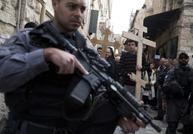 """Israeli border police stand on guard as Christian pilgrims from Serbia carry wooden crosses along Via Dolorosa, or """"The Way of Sorrow,"""" in the Old City of Jerusalem on April 14, 2017. (Photo by Heidi Levine/GroundTruth)"""