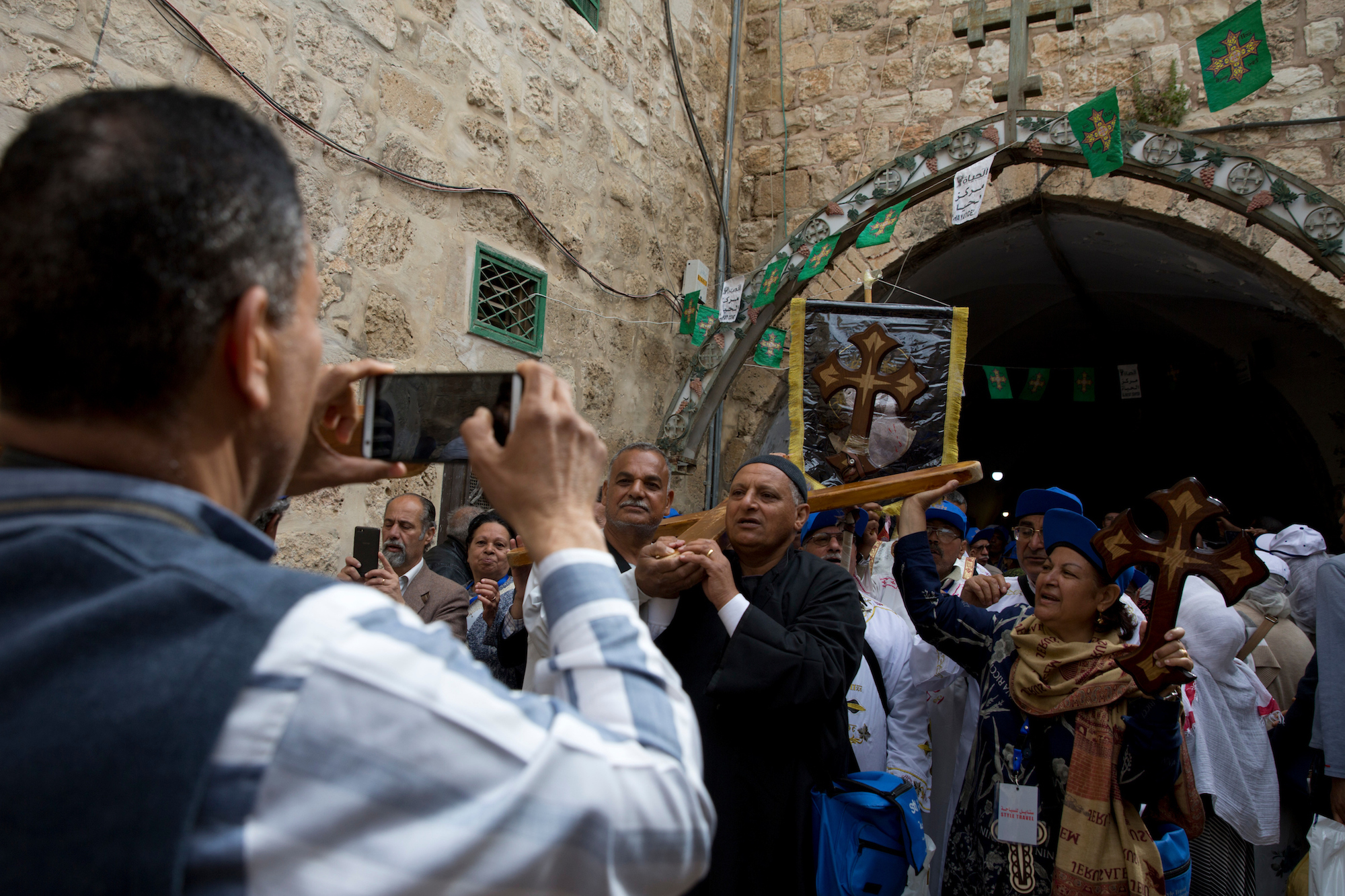 "Christian pilgrims walk along the Via Dolorosa, or ""The Way of Sorrow"" in the Old City of Jerusalem on Good Friday, April 14, 2017. Every year, thousands of Christians from around the world flock to the region to commemorate Easter, but residents say they hardly interact with Palestinian Christians who have carried the faith's tradition in the Holy Land. (Photo by Heidi Levine/GroundTruth)"