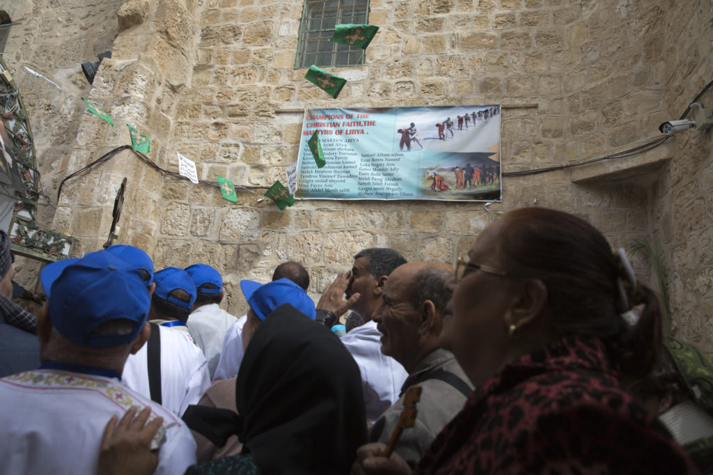 Egyptian Christian worshippers stand on the rooftop of the The Church of the Holy Sepulchre during Good Friday as they pass by a poster showing images from 2015 released by the Islamic State of Iraq and the Levant (ISIL) – Christian migrant workers that they had kidnapped in the city of Sirte, Libya (Photo by Heidi Levine)
