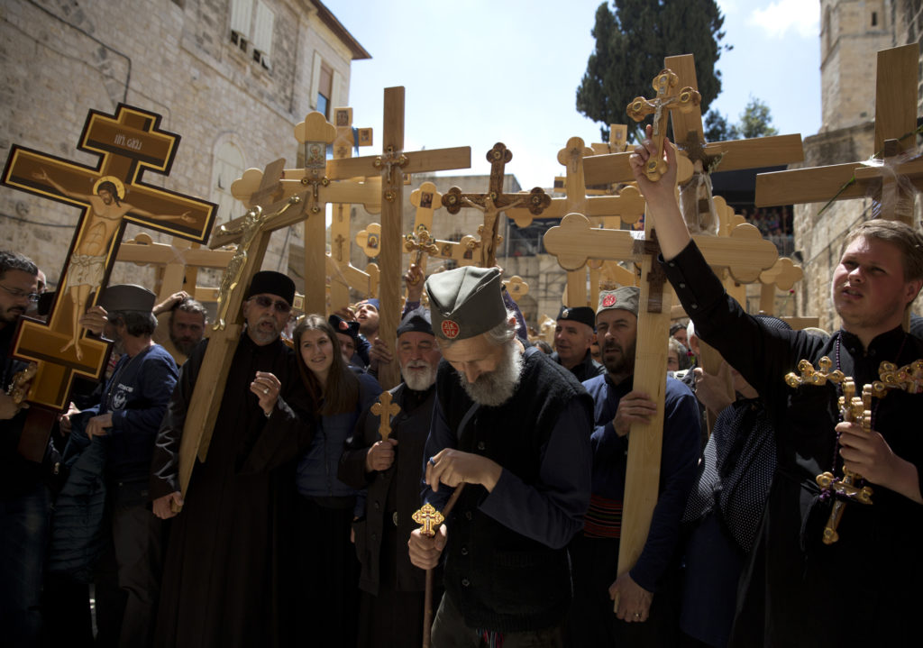 Christian Orthodox pilgrims from Serbia pray and sing, carrying wooden crosses before entering the Church of the Holy Sepulchre on April 14, 2017. (Photo by Heidi Levine)