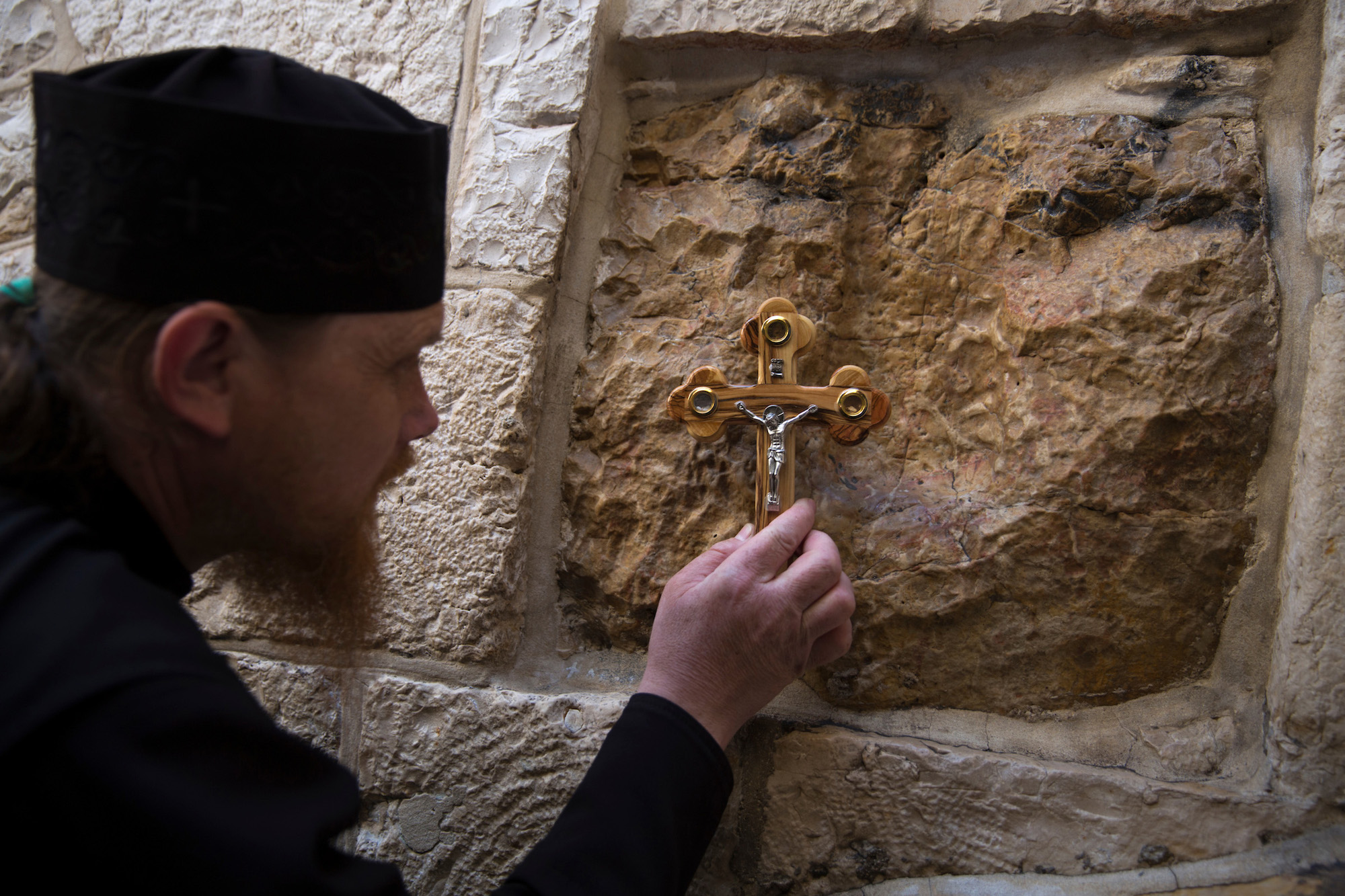 "An Orthodox Christian worshipper stops at one of the fourteen stations of the cross along the Via Dolorosa, or ""Way of Sorrow"", in the Old City of Jerusalem. On Good Friday, Christians around carry out a procession along the Via Dolorosa, which is believed to be the path that Jesus walked on the way to his crucifixion. Jerusalem, April 14, 2017. (Photo by Heidi Levine/GroundTruth)"