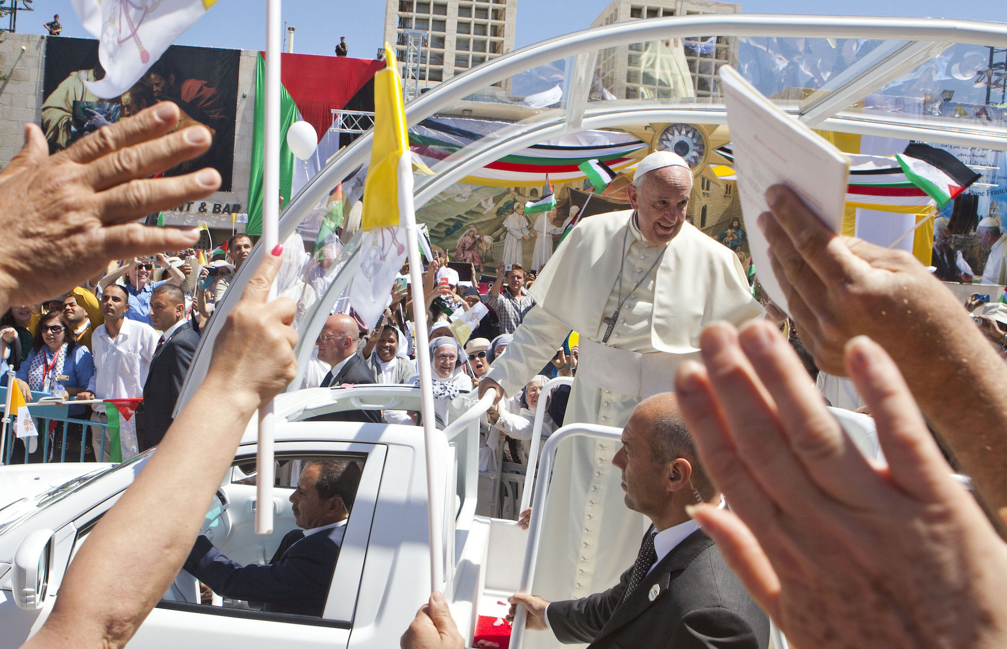 In an open vehicle, Pope Francis arrived in Bethlehem's Manger Square, which was packed with over 10,000 Christian pilgrims on Sunday, May 25, 2014. The visit marked the beginning of his three-day Middle East tour aimed at easing an ancient rift with Orthodox Christians and forging regional peace. (Photo by Heidi Levine/Sipa Press)