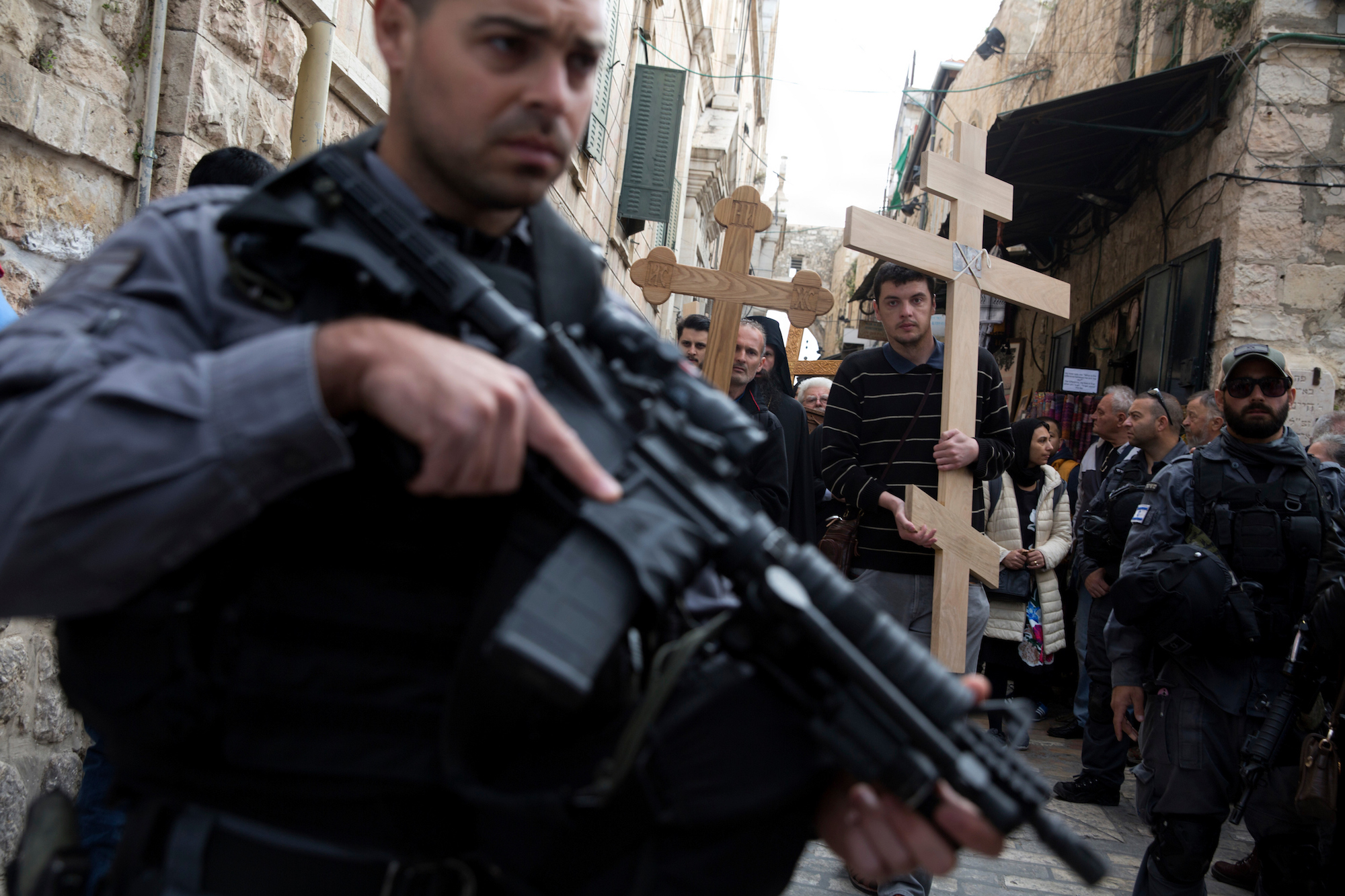 """Israeli border police stand guard as Christian pilgrims from Serbia carry wooden crosses along Via Dolorosa, or """"The Way of Sorrow"""" in the Old City of Jerusalem on April 14, 2017. Security was heightened in and around the Old City on Friday and through the Easter weekend after a 20-year-old British exchange student in Jerusalem was killed Friday in a stabbing attack, the latest in a reported wave of attacks by Palestinian militants that have taken the lives of 40 Israelis and two foreigners over the last 18 months. (Photo by Heidi Levine/GroundTruth)."""