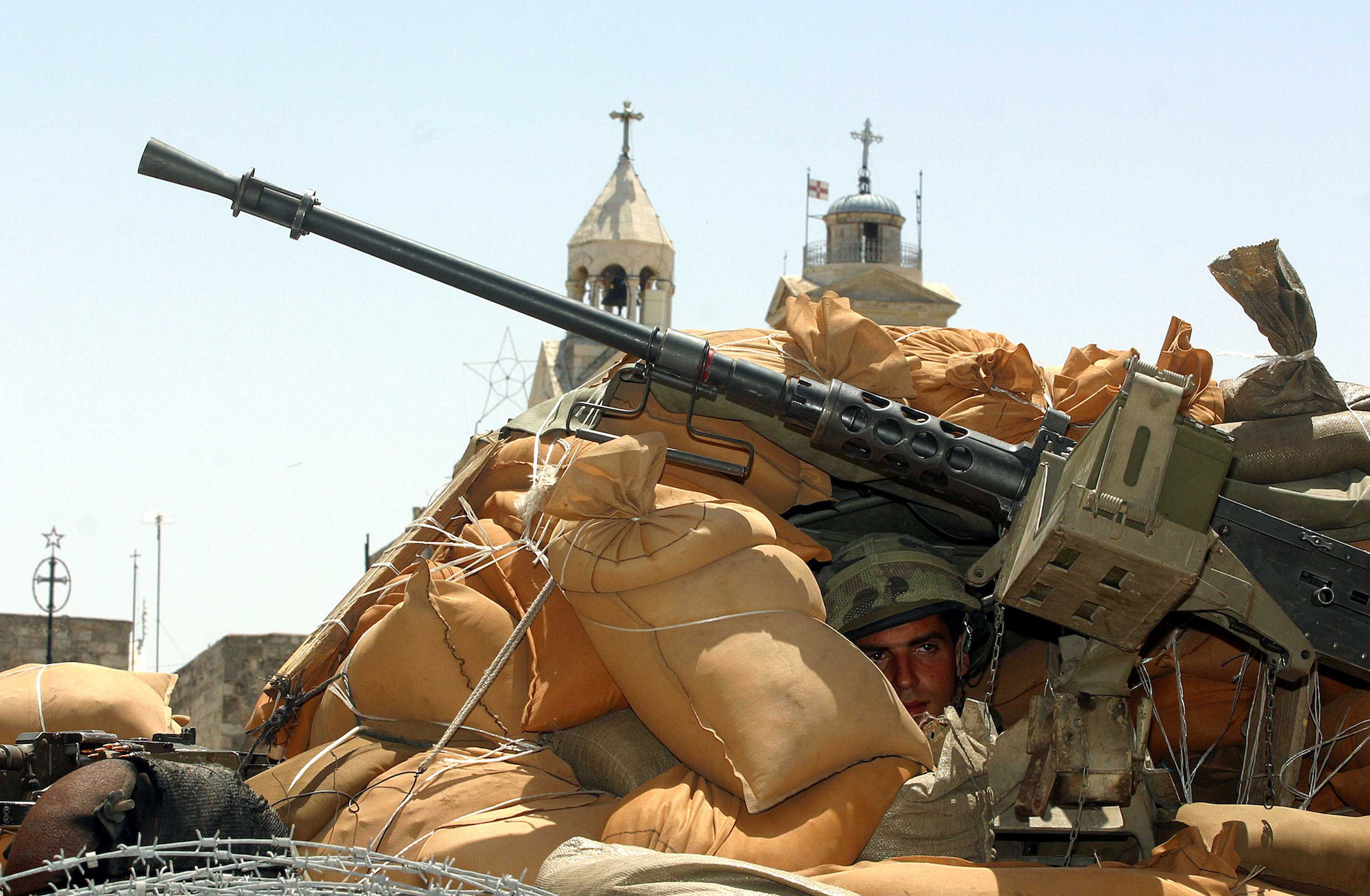 An Israeli soldier in an armored personnel carrier in front of the Church of Nativity in the biblical city of Bethlehem, where the Christian faith holds that Jesus Christ was born. Israeli forces entered the city in May 2002 in a wide-scale operation to arrest Palestinian militants. Bethlehem, May 2002 (Photo by Heidi Levine)