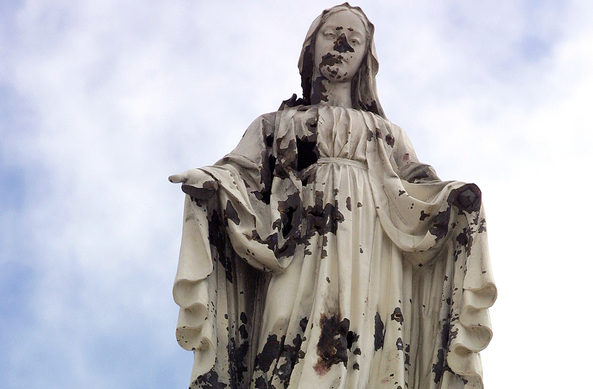 A damaged statue of the Virgin Mary stands atop the chapel of the Holy Family Hospital and Orphanage in Bethlehem. The statue was hit by shrapnel when a shell from an Israeli tank slammed into the church during a predawn attack on March 14, 2002. (Photo by Heidi Levine)