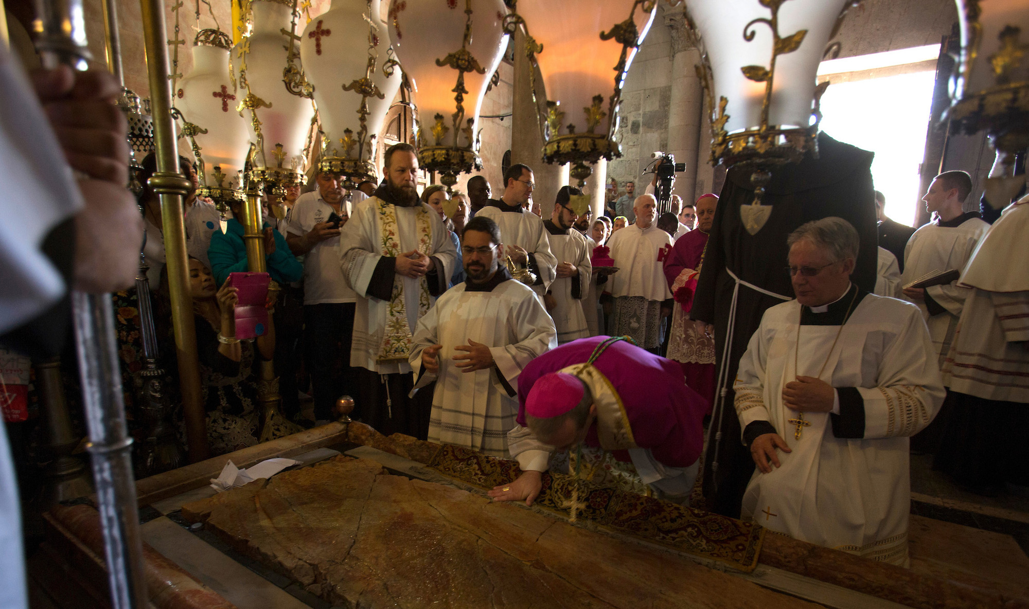 Latin Patriarch of Jerusalem, Pierbattista Pizzaballa (wearing pink), and other clergymen stand by the Stone of Unction during the Easter Sunday procession at the Church of the Holy Sepulchre, which is believed to be the site of the crucifixion and burial of Jesus Christ. Thousands of Christians from around the world flocked to Jerusalem to commemorate the day when, according to Christian tradition, Jesus resurrected. Jerusalem, April 16, 2017 (Photo by Heidi Levine/GroundTruth).