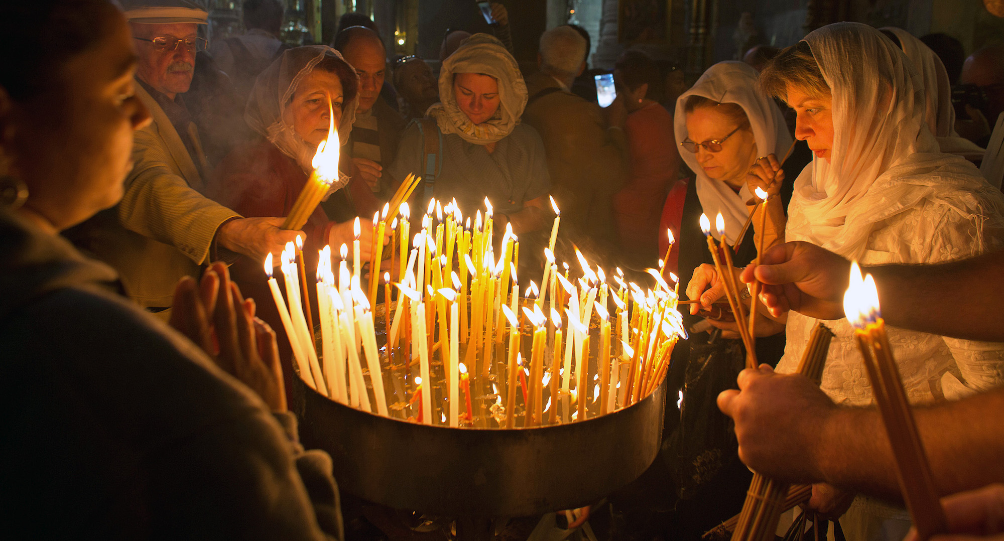 Christian pilgrims light candles during Easter Sunday at the Church of the Holy Sepulchre, traditionally believed by Christians to be the site of the crucifixion and burial of Jesus Christ. Thousands of Christians from across the world flocked to Jerusalem to commemorate the day when, according to Christian tradition, Jesus resurrected. Jerusalem, April 16, 2017 (Photo by Heidi Levine/GroundTruth).