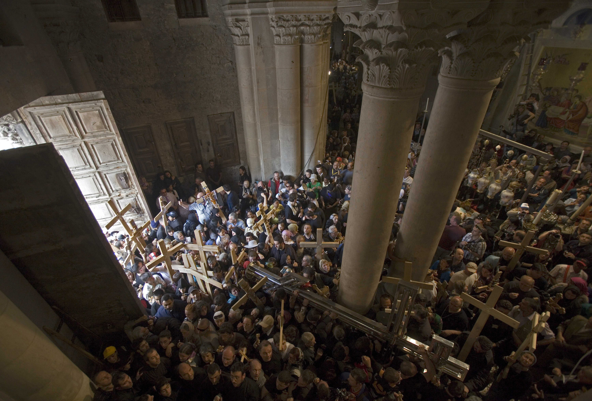 "Christian pilgrims carry crosses inside the Church of the Holy Sepulchre during a Good Friday procession in the Old city of Jerusalem on April 2, 2010. Christian worshippers retraced the route Jesus Christ took along the Via Dolorosa, or ""Way of Sorrow"", towards his crucifixion in the Church of the Holy Sepulchre. (Photo by Heidi Levine/Sipa Press)."