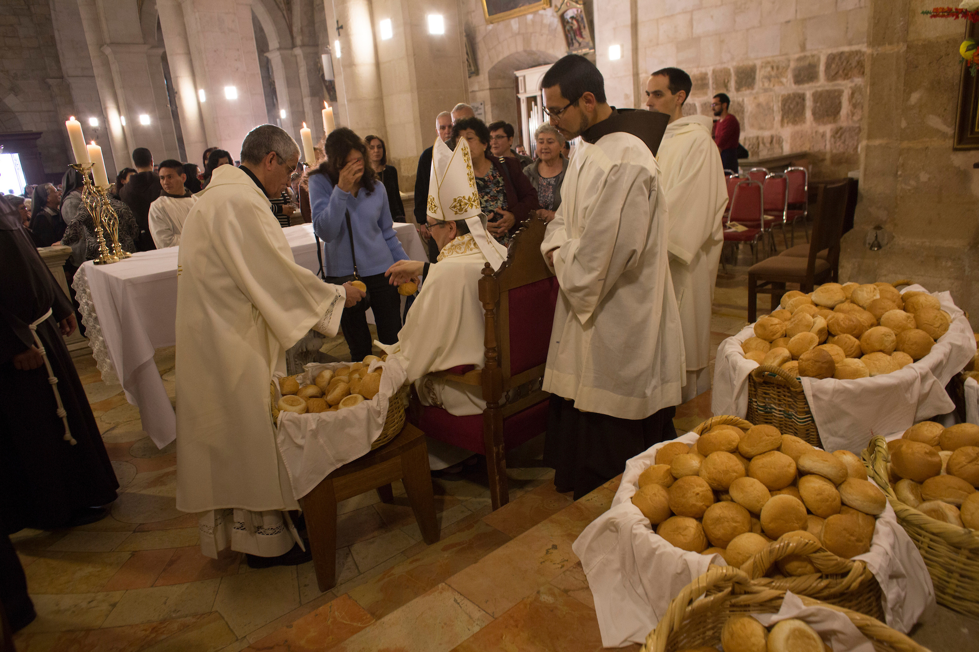 "Christian clergymen prepare to hand out Bethlehem-baked rolls of bread to worshippers in the Franciscan Church of Emmaus. The tradition honors the biblical story in which Jesus ""broke the bread"" with the disciples Cleopas and Simeon. Over a thousand Christian worshippers from across the West Bank and Jerusalem, as well as foreign pilgrims, attended the Mass in the West Bank village of El Qubeibeh on Monday, April 17, 2017.(Photo by Heidi Levine/GroundTruth)."