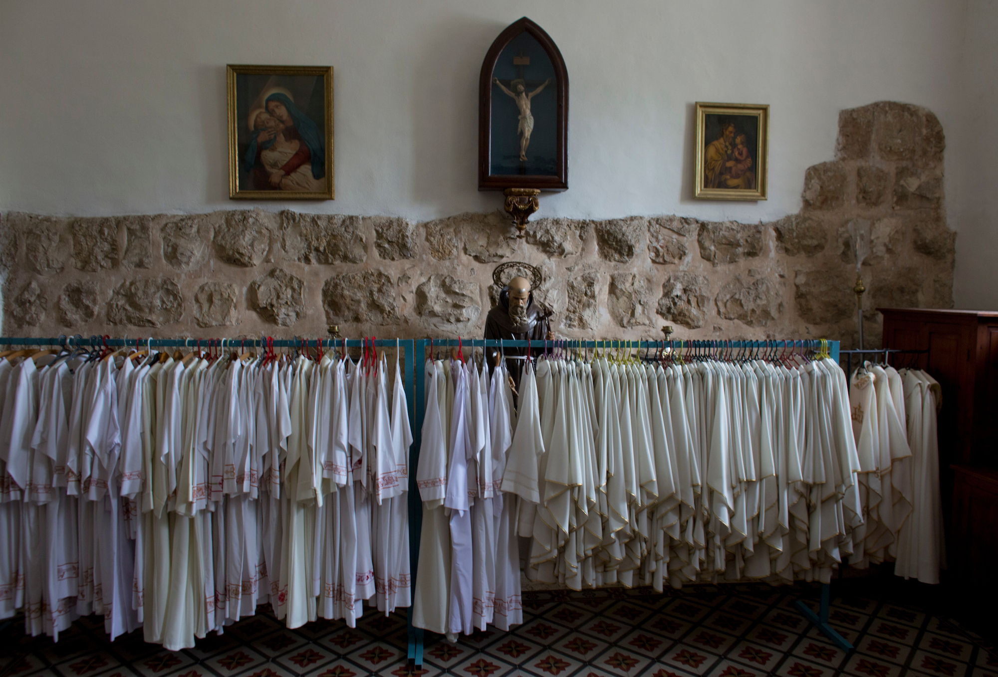 Priestly robes and a statue of Saint Francis are seen in the sacristy of the Franciscan Church of Emmaus in the West Bank village of El Qubeibeh, also known as Emmaus. On Monday April 17, 2017, over a thousand Christian pilgrims flocked to a Mass that celebrates the biblical story of The Road to Emmaus. (Photo by Heidi Levine/GroundTruth)