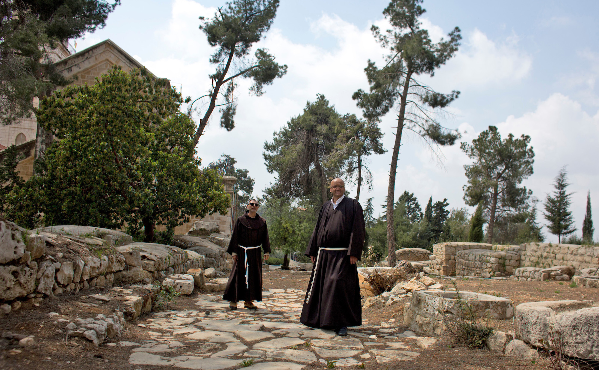 Father Salem Yunis, from Aleppo, Syria (R), and Father Oscar Rodriguez, from El Salvador (L), stand on the remnants of an ancient Roman road in Emmaus, which today lies in West Bank territory.