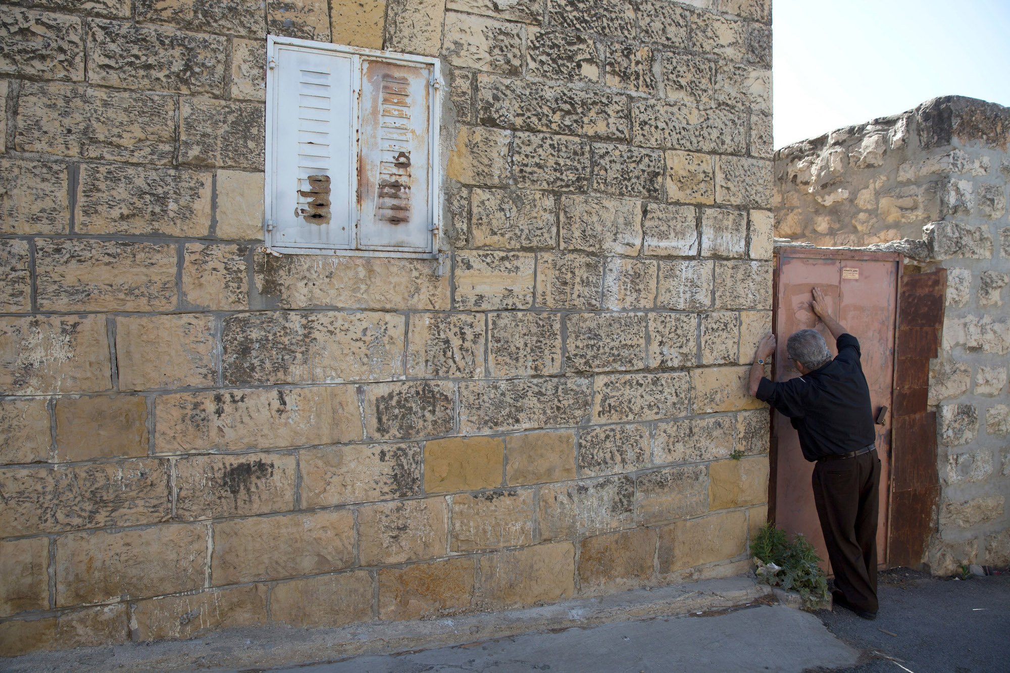 Anton Qulibyoba Yoakim, 63, bangs on the metal door of the home he grew up in the West Bank village of El Qubeibeh, on Monday, April 17, 2017. He now lives in the Old City of Jerusalem with his family. (Photo by Heidi Levine/GroundTruth)