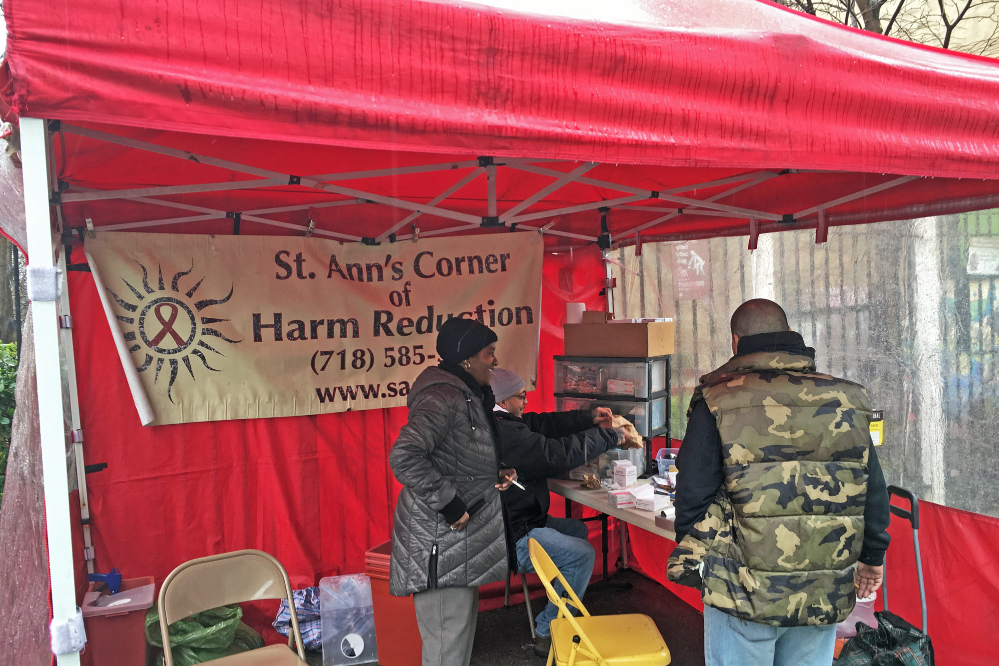 Deborah Walker and Eddie Morales work under the tent at St. Ann's Corner. (Photo by Michael O'Brien/GroundTruth)