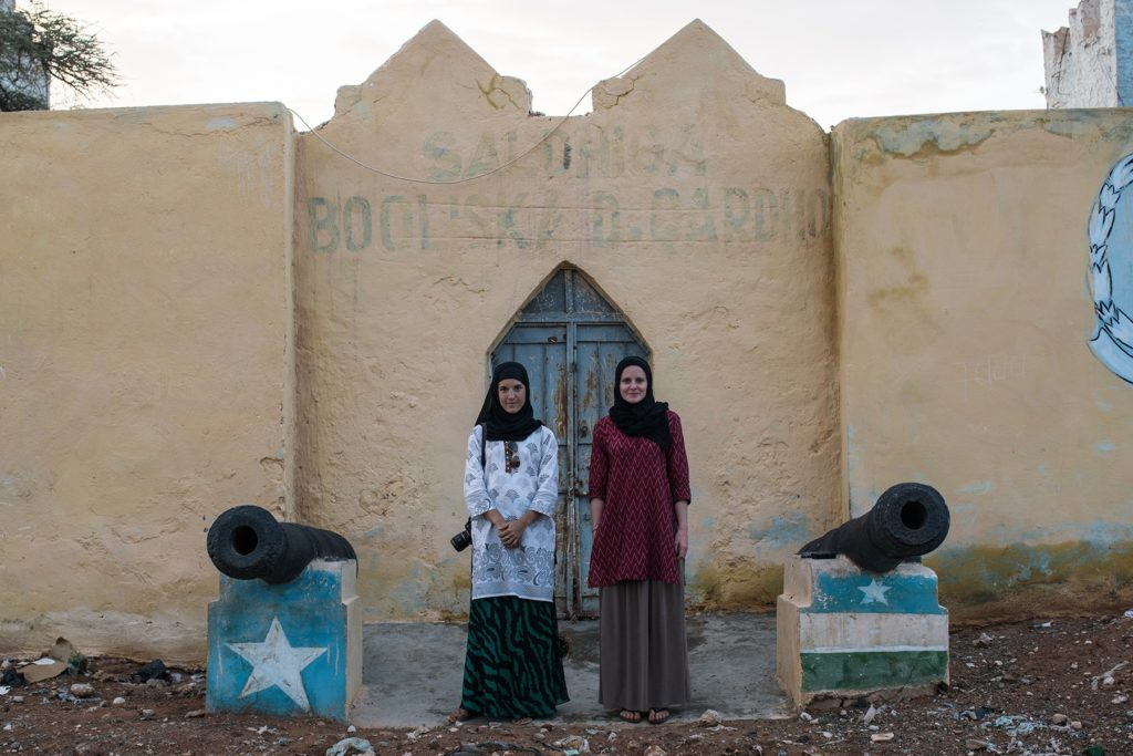GroundTruth fellows Nichole Sobecki (left) and Laura Heaton (right) stand between two cannons on their reporting trip to Somalia, where they documented links between drought and violent conflict.
