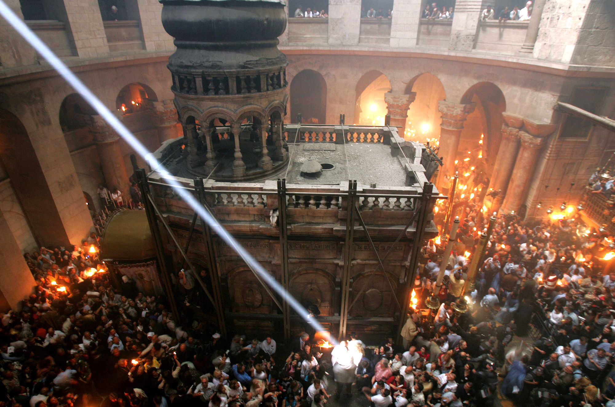 A single shaft of sunlight streams into the Church of the Holy Sepulchre, illuminating the spot where fire erupted from the Tomb of Christ during the ceremony of the Holy Fire on Saturday, the day before Orthodox Christian Easter, in 2005. Fire comes from within the tomb and is quickly spread to candles held by the faithful of Greek Orthodox, Armenian and Coptic denominations. More than 10,000 Orthodox pilgrims filled the church that year. Jerusalem, April 30, 2005 (Photo by Heidi Levine/Sipa Press).