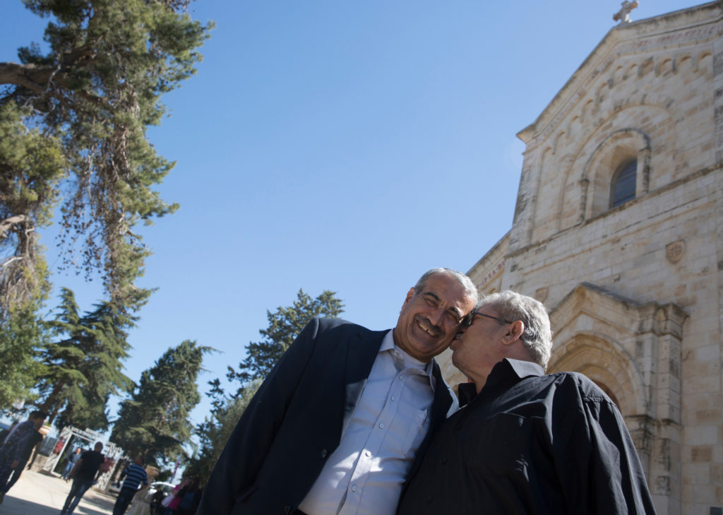 Anton Qulibyoba Yoakim, 63, (right) kisses his friend Baker Ma'Ali, 63, at the Franciscan Church of Emmaus in the West Bank village of El Qubeibeh on Monday, April 17, 2017. Anton recalled how they both breastfed from each other's mother when they were babies. (Photo by Heidi Levine/GroundTruth)