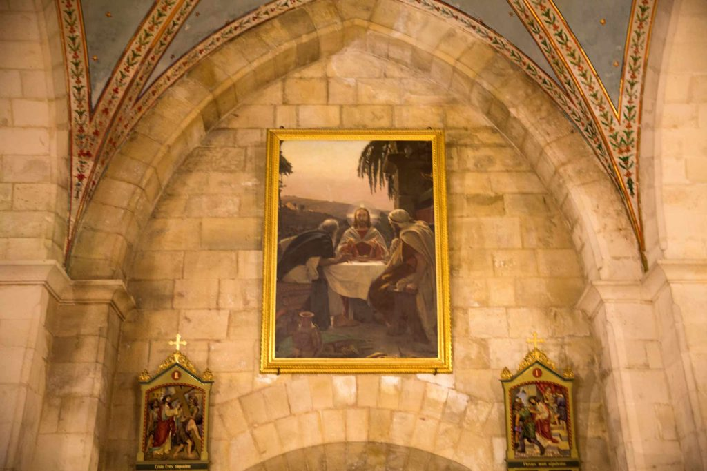 A painting depicts Jesus breaking bread with the disciples Simeon and Cleopias in the biblical town of Emmaus, in the Franciscan Church of Emmaus. El Qubeibeh, April 15, 2017. (Photo by Heidi Levine/GroundTruth)