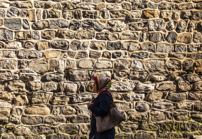 A woman walks alongside a brick wall (Photo via Pixabay)