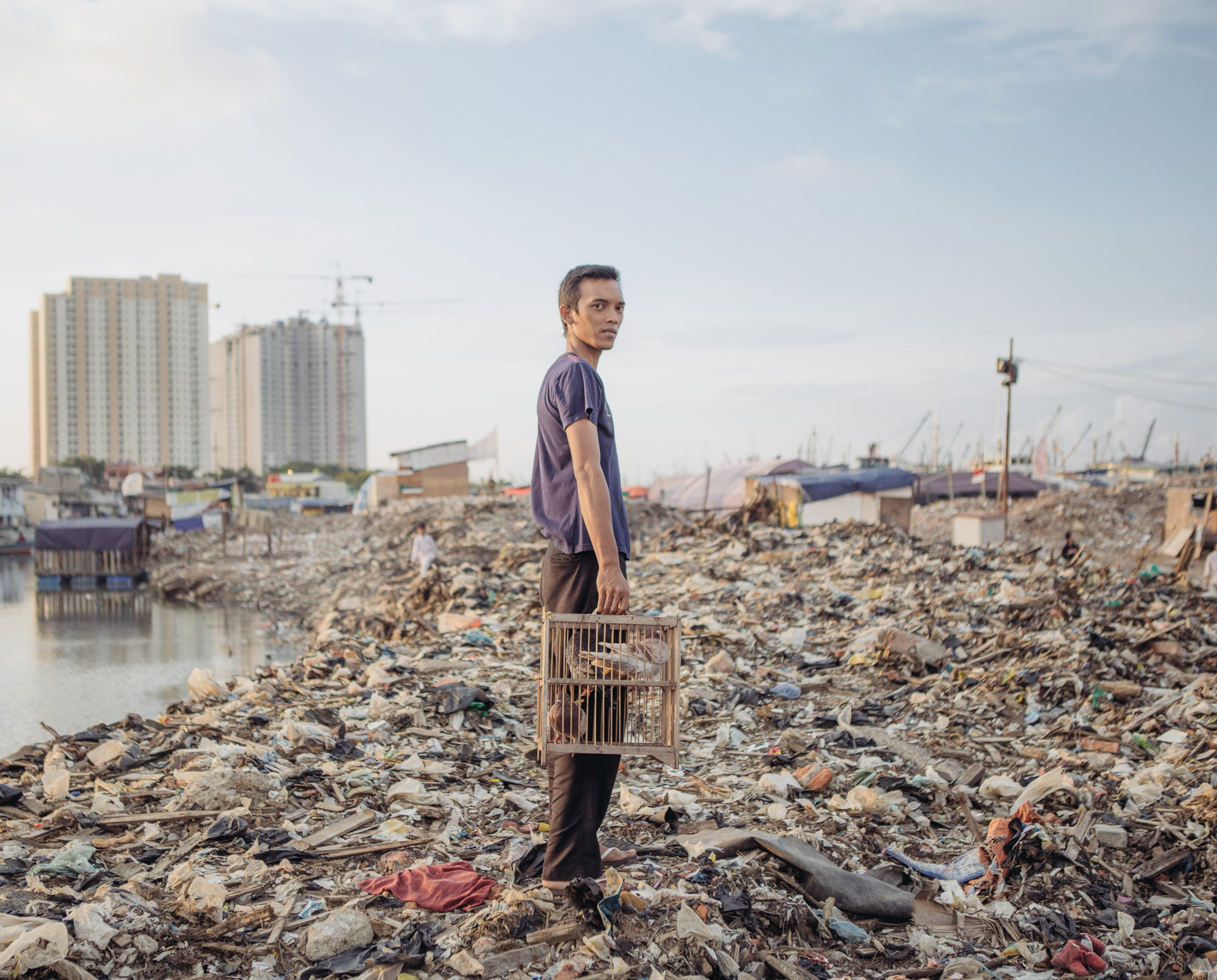 A man with his pigeons posed for photographs in Pasar Ikan district of North Jakarta. As part of Jakarta's river revitalization project, a settlement in this district was recently razed, leaving its residents homeless. It's part of an effort to combat sea level rise, worsened by climate change. (Photo by Muhammad Fadli/GroundTruth)