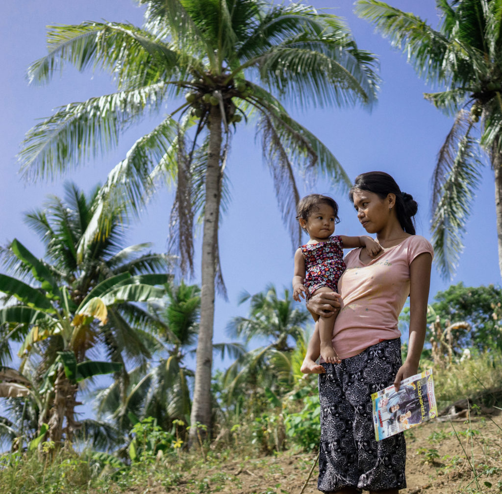 A mother holds her baby in the Philippines, where climate change is driving waves of human trafficking. Click on the photo to see the story. (Photo by Hannah Reyes Morales/GroundTruth)