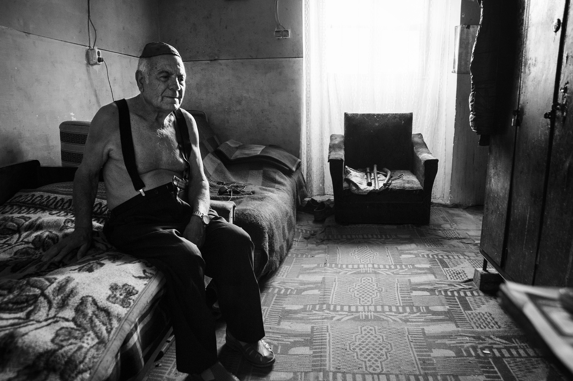 Alexandru Kepes, 79, a survivor of the Holocaust, sits in his small apartment in the back of the empty Zion Neologic Synagogue keeping watch of the sanctuary and scaring away any would-be vandals on Aug. 19, 2013. (Photo by Daniel Owen/GroundTruth)