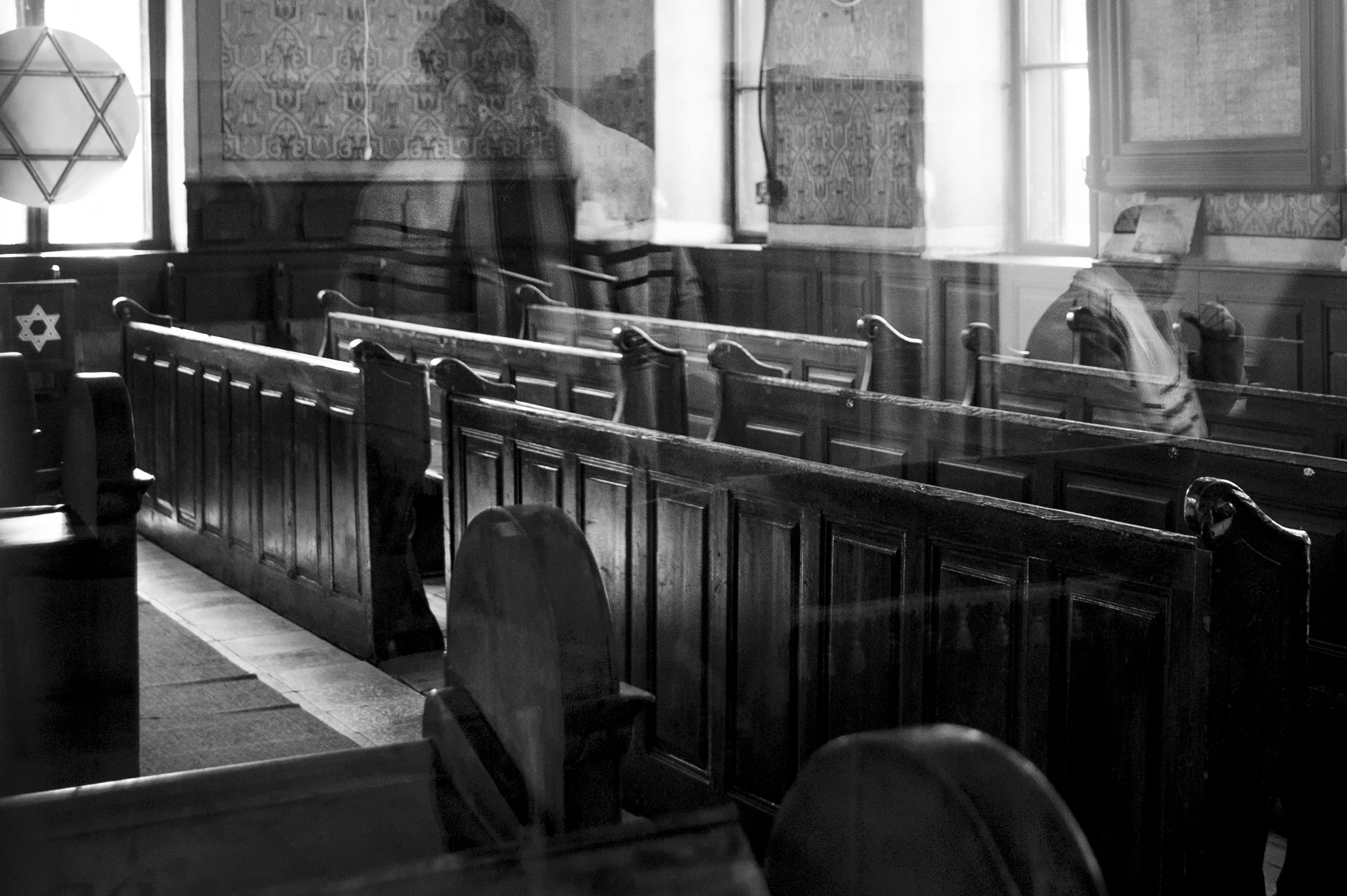 During the weekly Torah reading in Oradea, Romania's last functioning synagogue, reflections fill the empty Sas Chevra Synagogue sanctuary like reminders of a former community; April 11, 2013. Most of the over 30,000 Jews from Oradea at the time of the war were deported to Nazi camps across Europe. (Photo by Daniel Owen/GroundTruth)