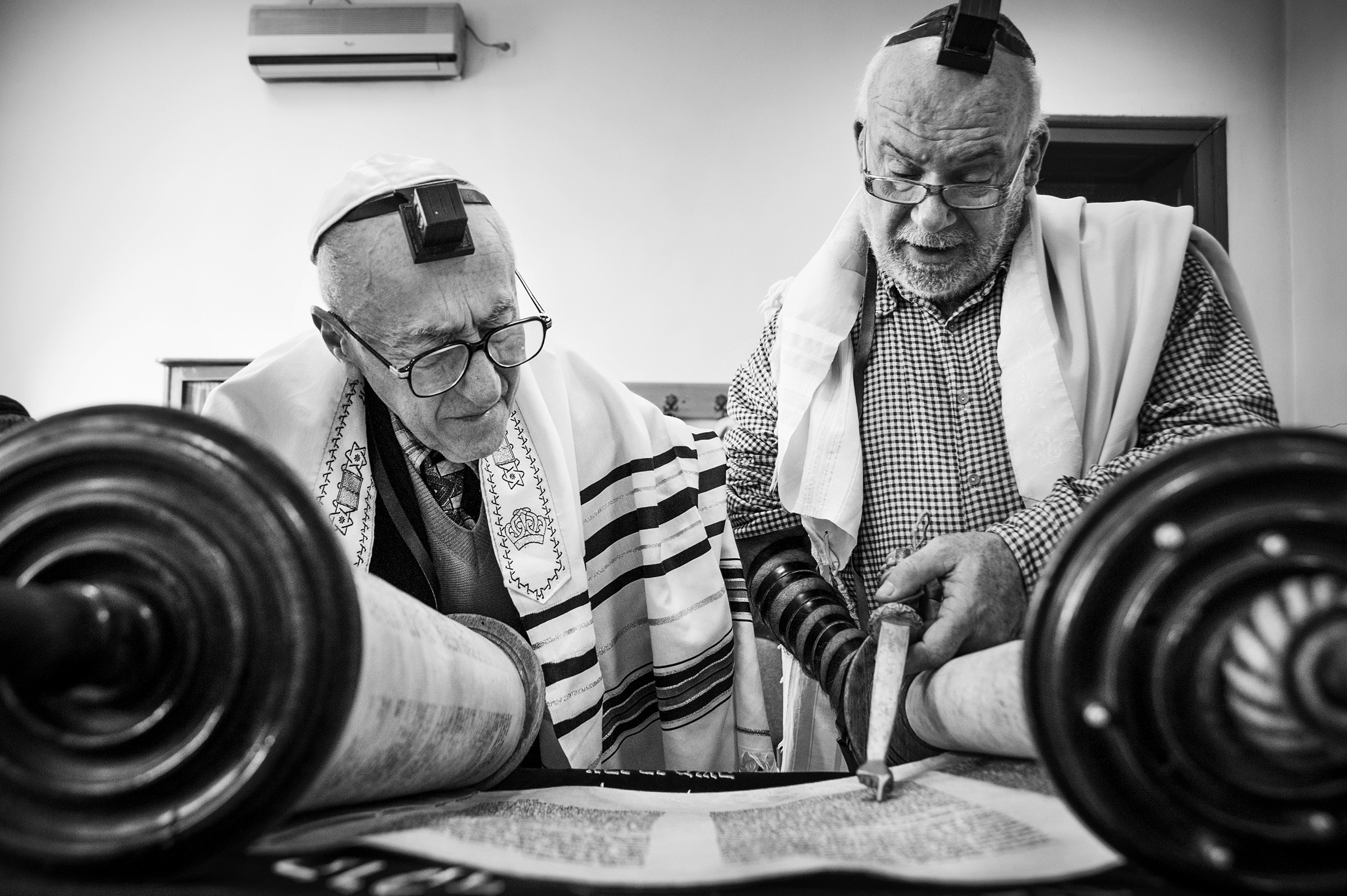 Community member, Zakaria Salman, left, and Cantor Shraya Kav, right, read from the Torah scroll during the daily morning meeting at the Sas Chavra Synagogue on April 11, 2013. Though not officially a rabbi, Kav, a cantor from Tel Aviv, performs many of daily duties of a rabbi for the small community. (Photo by Daniel Owen/GroundTruth)