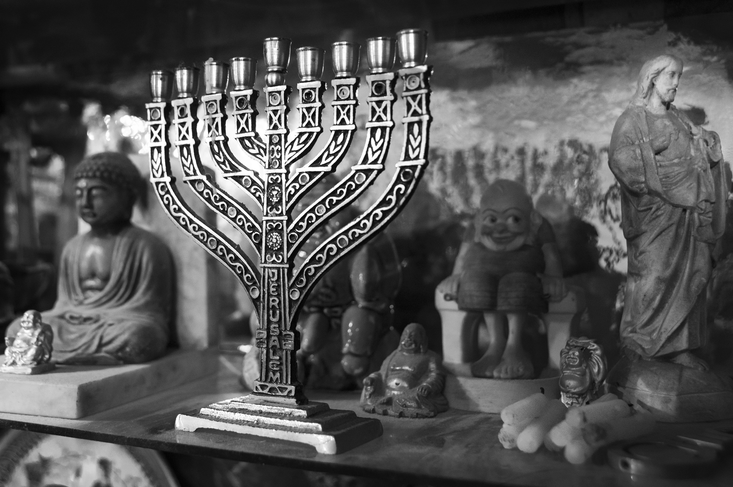 "The menorah stands on a crowded shelf in the home of Paul Spitzer (not pictured), the son of Holocaust survivor Amram Yehekztel on January 7, 2015. Though now a regular member at the community center in Oradea, Spitzer grew up without practicing the many religious traditions of Judaism, but credits his daughter with bringing him back to his roots. ""I believe the community has a future. I don't know how it will happen, but it's like a branch that has been broken, but the seed has survived."" explains Spitzer. (Photo by Daniel Owen/GroundTruth)"