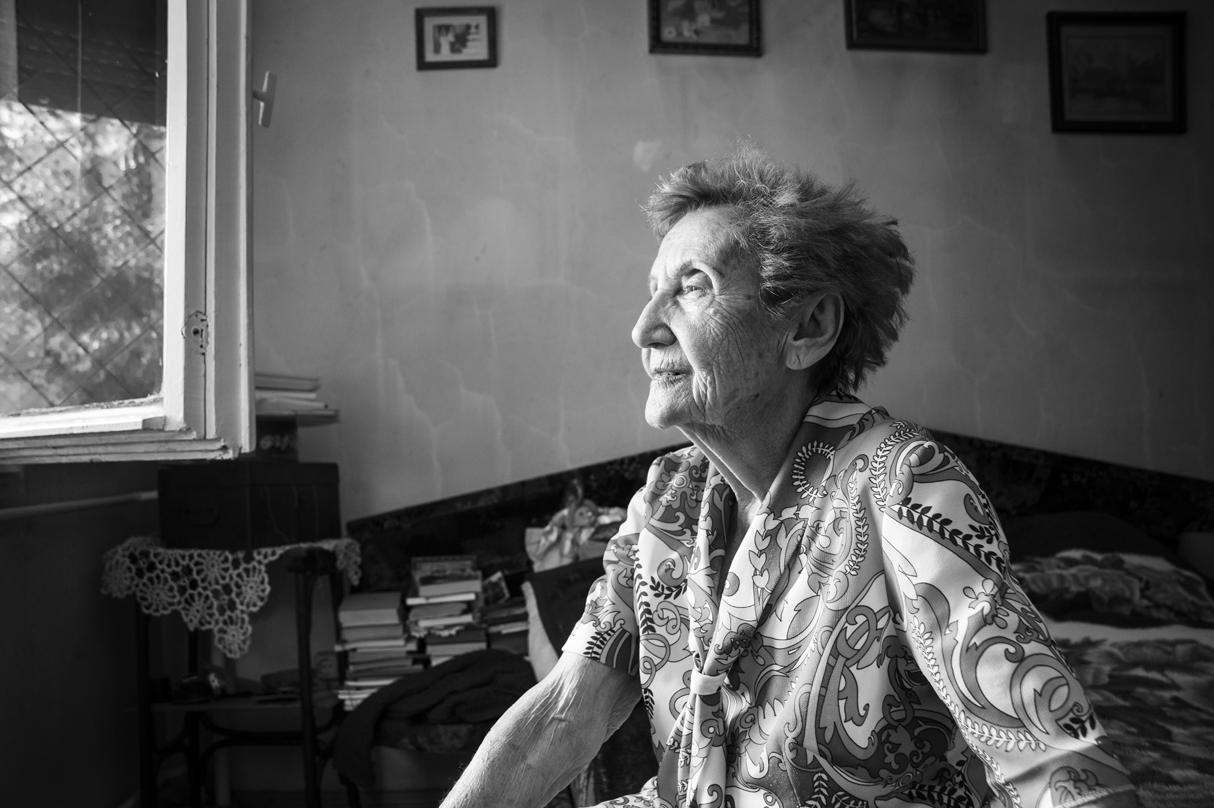 "Gabriella (Hamlet) Bóné, a survivor of Auschwitz Birkenau, sits on her bed and looks out the window of her small ground-level apartment in Oradea, Romania on August 23, 2013. Bóné vividly remembers the deportations when she was just fifteen years old. ""The Hungarian police crammed us into wooden train cars that had barbed wire covering the small windows. We traveled without food and with very little water for nearly a week without knowing what fate lay before us. We arrived at Auschwitz having barely slept only to be inspected by Dr. Mengele himself and the other SS officers."" (Photo by Daniel Owen/GroundTruth)"