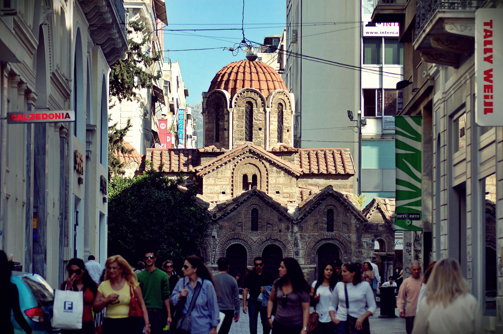 People shop on a busy street with Athen's 11th-century Byzantine Church of Panaghia Kapnikarea behind them. (Photo by Ananabanana/Flickr User)